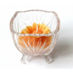Scented candle in the form of a flower of orange color in a nice glass container