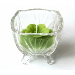 Scented candle in the form of a flower of green color in a pretty glass container