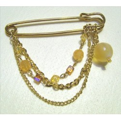 Golden pin decorated with pearls and chains